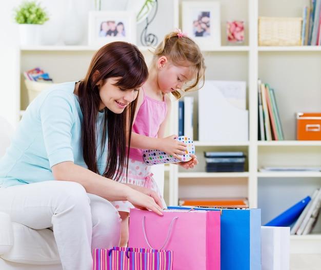 Молодая мать с маленькой дочкой дома с покупками - в помещении