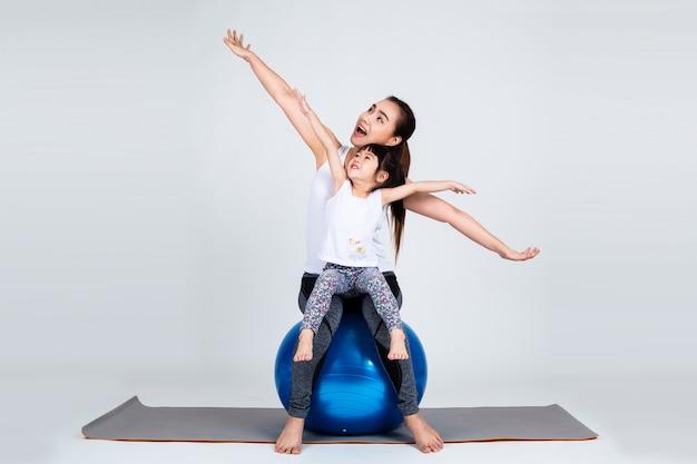 フィットネスボール運動の小さな娘を持つ若い母親