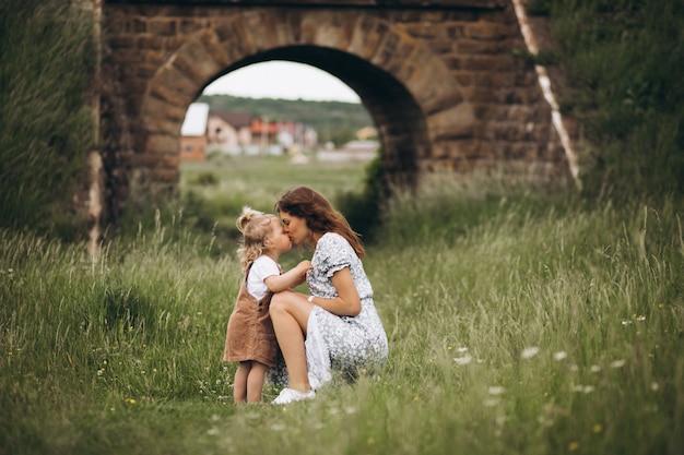公園で小さな娘を持つ若い母親