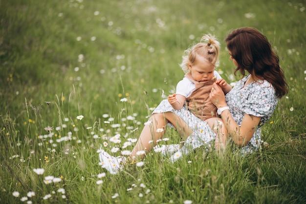 Giovane madre con la piccola figlia nel parco che si siede sull'erba