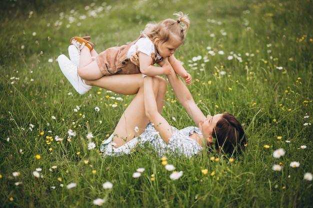 Young mother with little daughter in park sitting on grass