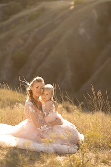 Young mother with a little daughter in pink dresses are sitting in the field. mom hugs daughter, hugging her