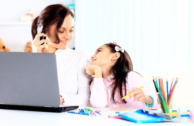 Молодая мать с маленькой дочерью, сидя вместе дома