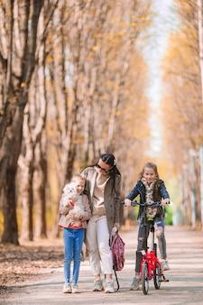 Молодая мать с маленькими девочками в осеннем парке в солнечный день. семья наслаждается теплой погодой в сентябрьский день
