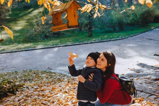 Молодая мама с маленьким ребенком положить семена в кормушку для птиц. осенний сезон