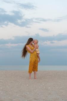 Молодая мать с длинными волосами, держа ребенка на пляже. вертикальная рама.
