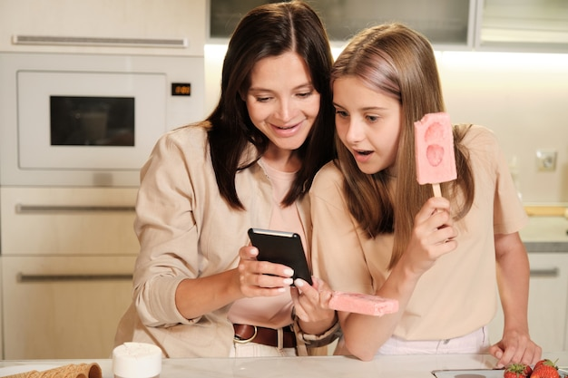 Young mother with smartphone showing her surprised teenage daughter curious online video while both having homemade icecream