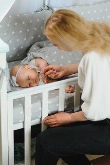 Молодая мать с новорожденным ребенком возле кроватки