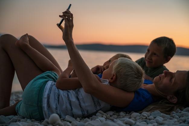 小石のビーチで横になっている3人の子供を持つ若い母親