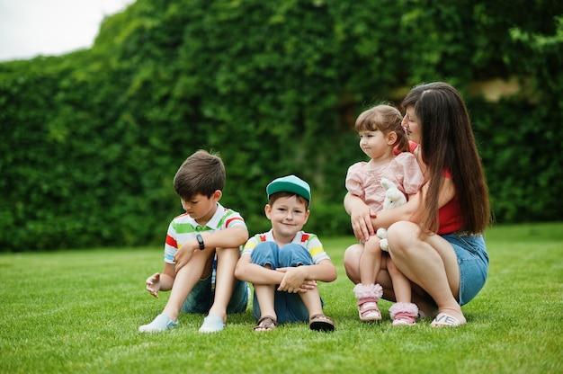 中庭の緑の芝生に座っている3人の子供を持つ若い母親。