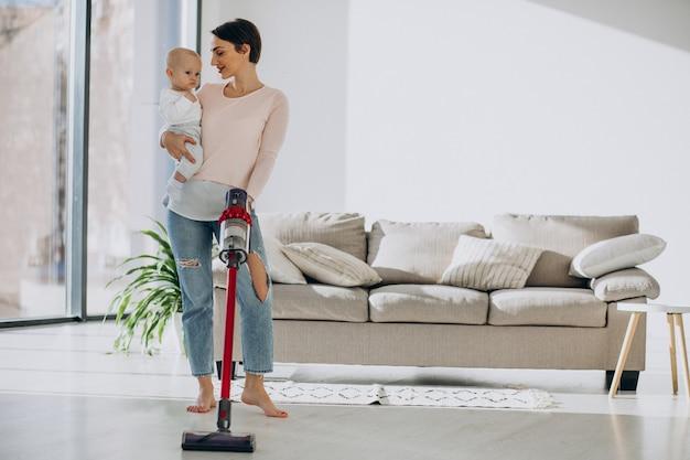 家で掃除する幼児の息子を持つ若い母親