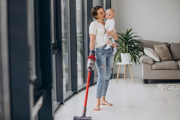 집에서 청소하는 유아 아들과 함께 젊은 어머니