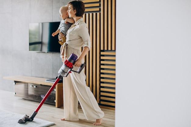 幼児の息子が家で掃除をしている若い母親