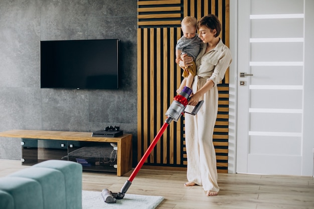 Young mother with toddler son cleaning up at home