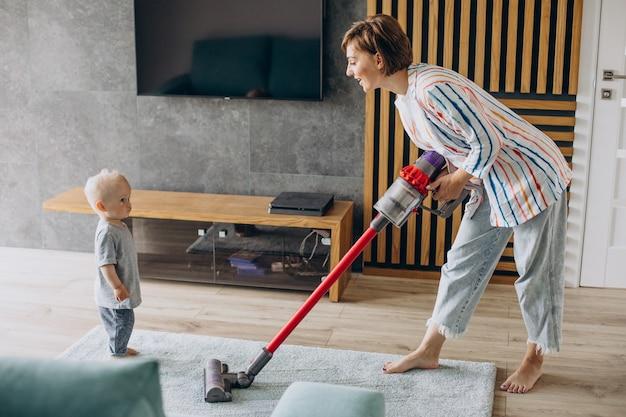 Giovane madre con figlio piccolo che fa le pulizie a casa