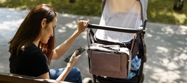 若い母親、公園のベンチに座っている手にスマートフォンを持つベビーカーを持つ女性