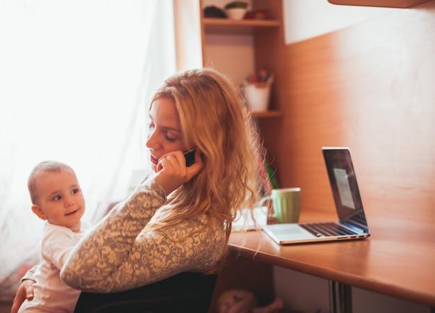 그녀의 팔에 딸을 안고 일하는 젊은 어머니