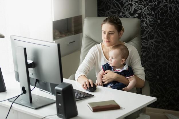 ホームオフィスで働き、赤ん坊の息子の世話をしている若い母親 Premium写真