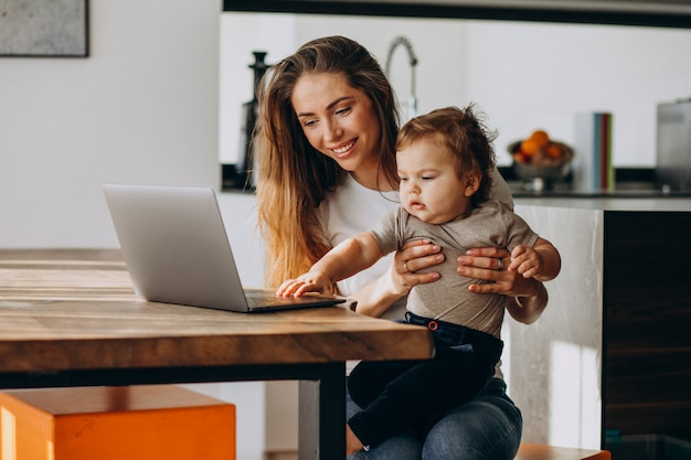 Young mother working from home on laptop with her little son