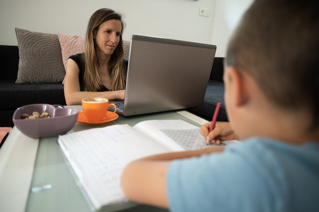 Young mother working from home using laptop computer homeschooling her son at the same time.
