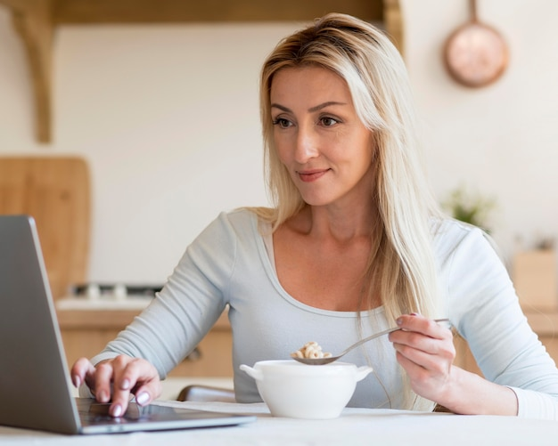 Young mother working and having breakfast at home