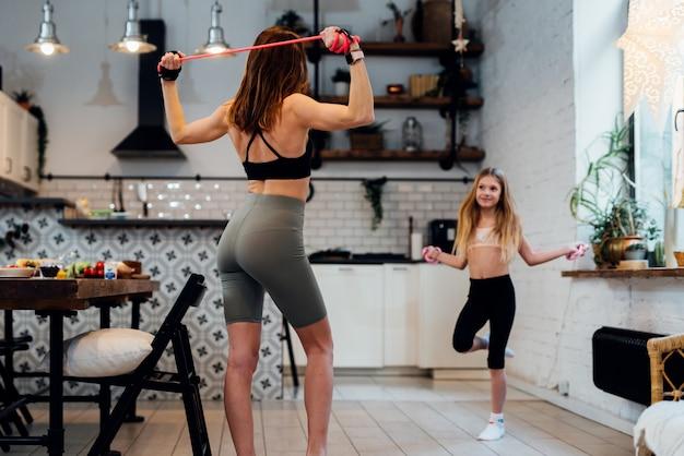 그녀의 딸과 함께 집에서 운동 하는 젊은 어머니.