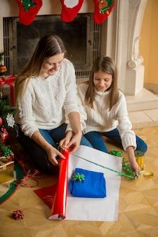 彼女の娘とクリスマスプレゼントを包む若い母親