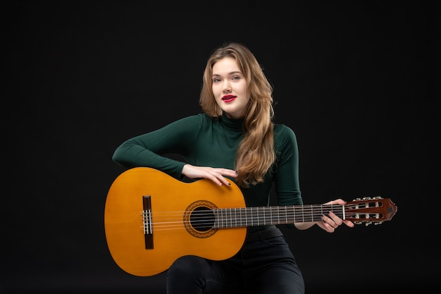 Young motivated female guitarist holding her favorite musical instrument on dark