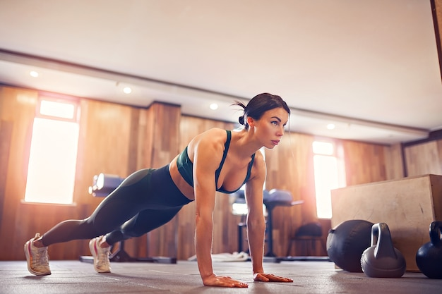Young motivated girl doing plank exercise at gym, full length photo, copy space