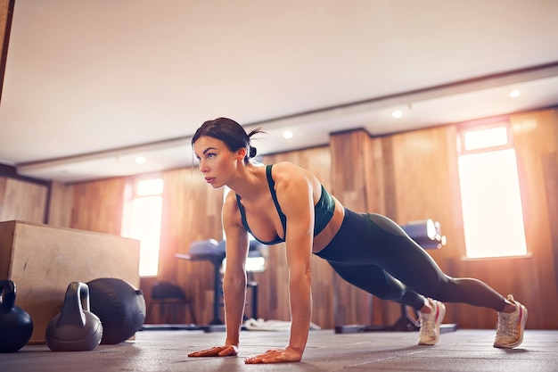 Young motivated girl doing plank exercise at gym