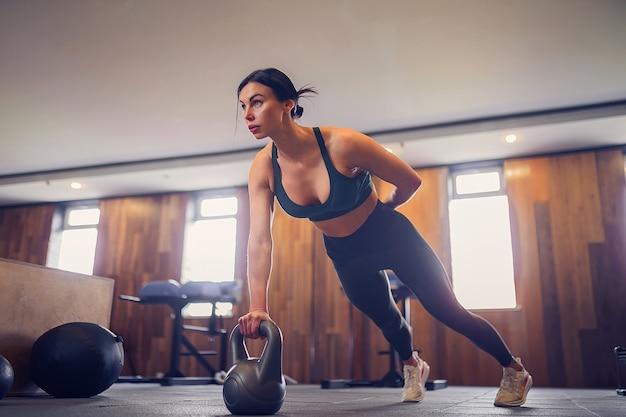 체육관에서 한 손으로 kettlebells를 사용하여 판자 운동을하는 젊은 동기 부여 소녀, 전체 길이 사진, 복사 공간