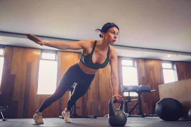 Young motivated girl doing plank exercise using kettlebells with one hand at gym