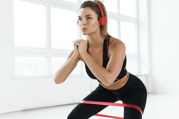 Young motivated woman listening music during her workout with a loop resistance band