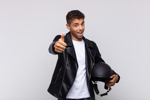 若いバイクライダーは、誇り高く、のんきで、自信を持って幸せに感じ、親指を立てて前向きに笑っています