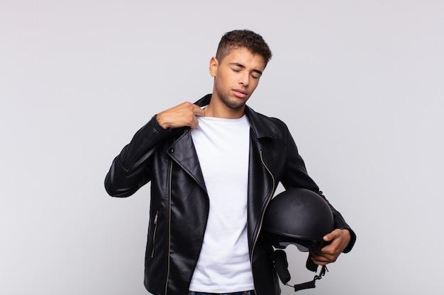 若いバイクのライダーは、ストレス、不安、疲れ、欲求不満を感じ、シャツの首を引っ張って、問題で欲求不満に見えます