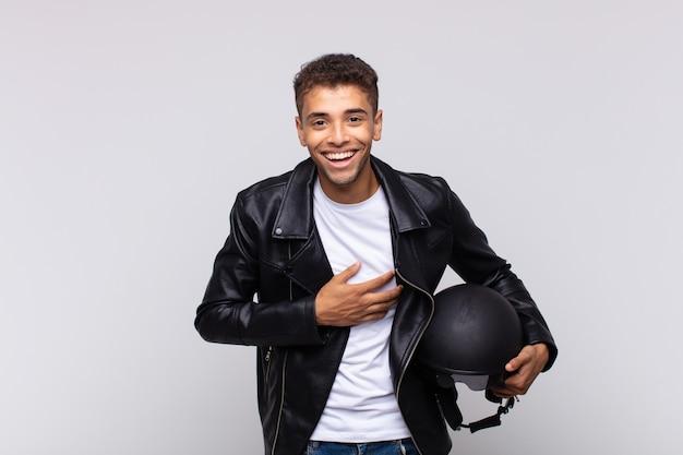 いくつかの陽気な冗談で大声で笑い、幸せで陽気に感じ、楽しんでいる若いバイクライダー