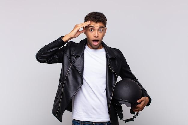 幸せそうに見えて、驚いて、驚いて、笑顔で、驚くべき信じられないほどの良いニュースを実現している若いバイクライダー
