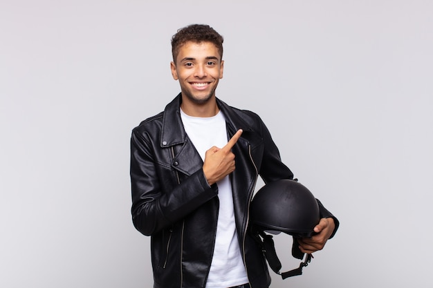 Молодой мотоциклист весело улыбается, чувствует себя счастливым и указывает в сторону и вверх, показывая объект в пространстве для копирования
