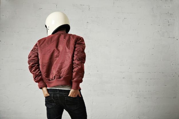 흰색 헬멧과 빨간색 나일론 재킷을 입은 젊은 오토바이 운전자는 흰색 벽이있는 스튜디오에서 청바지 뒷주머니에 손을 넣고 뒤에서 촬영했습니다.
