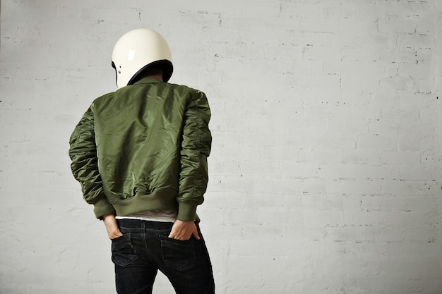 Young motorcyclist in white helmet and green jacket portrait from the back with his hands in the back pockets of his jeans with white walls.