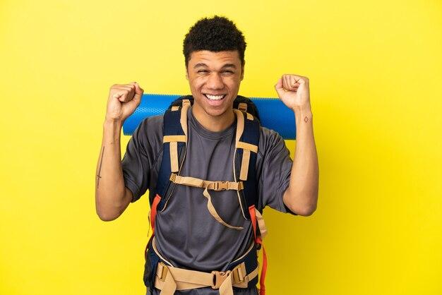 勝者の位置での勝利を祝う黄色の背景に分離された大きなバックパックを持つ若い登山家アフリカ系アメリカ人の男