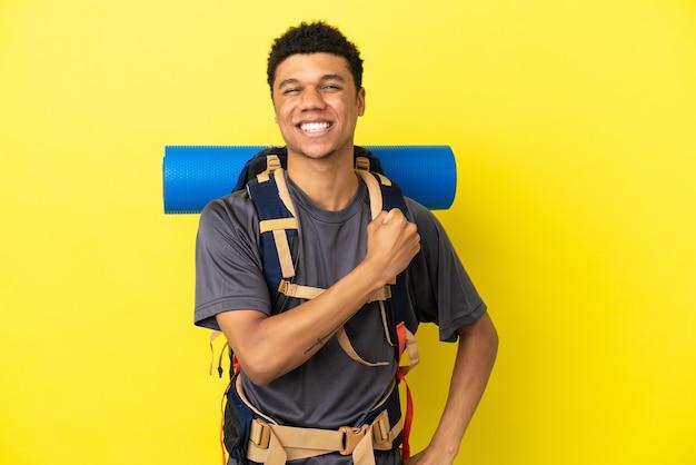 勝利を祝う黄色の背景に分離された大きなバックパックを持つ若い登山家アフリカ系アメリカ人の男