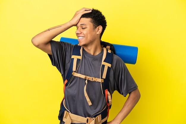 Молодой альпинист афроамериканец с большим рюкзаком на желтом фоне кое-что понял и намеревается найти решение