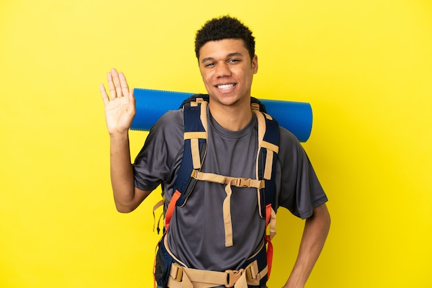 Молодой альпинист афроамериканец с большим рюкзаком на желтом фоне салютует рукой с счастливым выражением лица