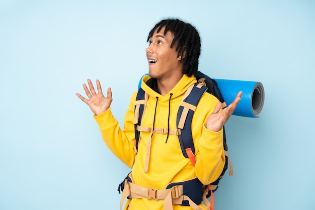 Young mountaineer african american man with a big backpack isolated on a blue background with surprise facial expression