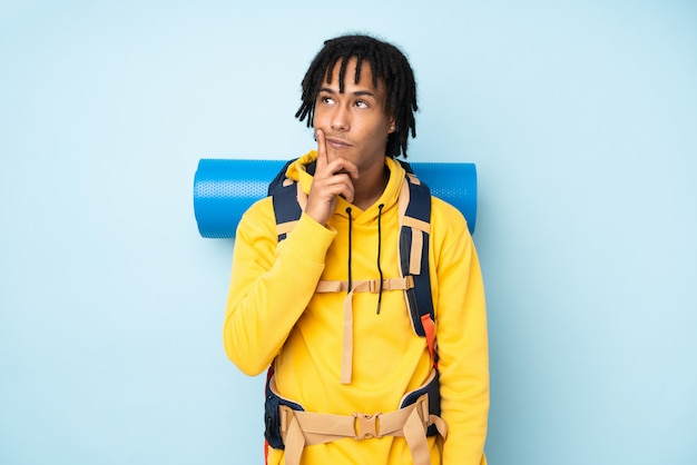 Young mountaineer african american man with a big backpack isolated on a blue wall thinking an idea