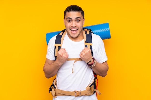 勝利を祝う黄色の背景に分離された大きなバックパックを持つ若い登山家アジア人男性