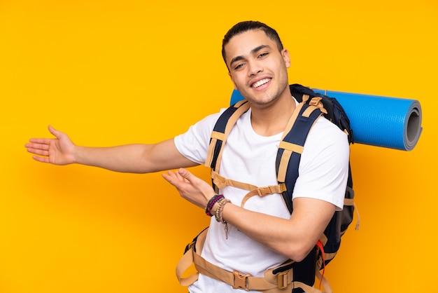 노란색 배경에 고립 된 큰 배낭 젊은 산악인 아시아 남자와 서 초대를 위해 손을 옆으로 확장