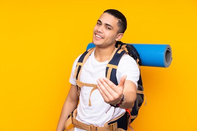 와 서 초대하는 노란색 벽에 고립 된 큰 배낭 젊은 산악인 아시아 남자