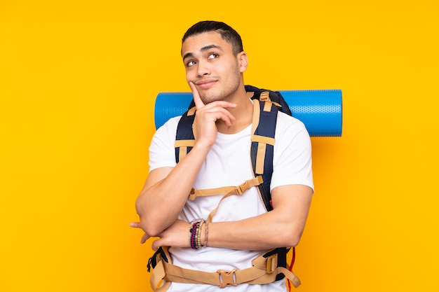 Young mountaineer asian man with a big backpack isolated on yellow wall thinking an idea